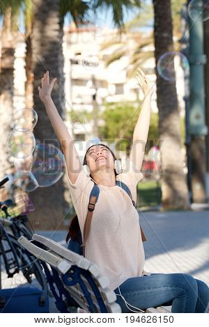 Happy Young Woman With Headphones And Arms Outstretched