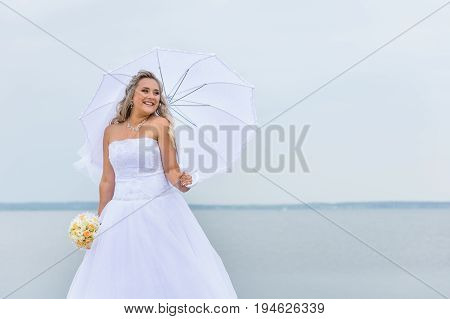 Beautiful bride in white dress with white umbrella and wedding bouquet of yellow and pink flowers, Lake Shore. Elegant bride outdoor wedding portrait. Wedding and honeymoon concept. Wedding day.
