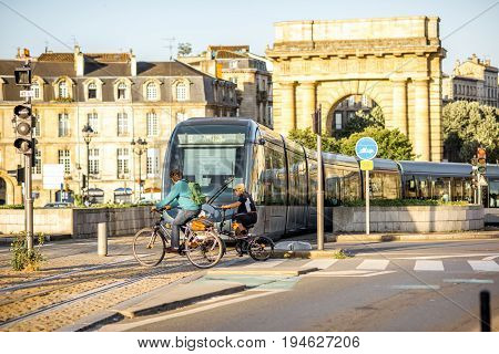 BORDEAUX, FRANCE - May 24, 2017: View on the famous Bourgogne gates with tram and people on the bicycles during the morning light in Bordeaux city, France