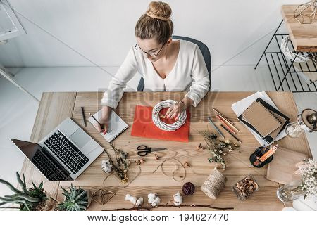 Top View Of Blonde Female Florist Working With Laptop And Dry Flowers At Workplace