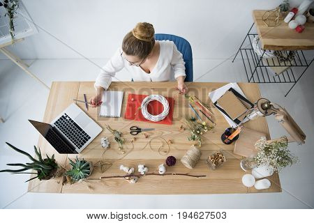 Overhead View Of Female Decorator With Wreath, Dry Flowers And Laptop At Workplace