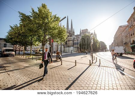BORDEAUX, FRANCE - May 24, 2017: Businessman cross the street with saint Pierre cathedral on the background during the sunny morning in Bordeaux city, France
