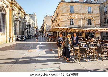 BORDEAUX, FRANCE - May 24, 2017: Business people standing near the cafe on the square at the old town of Bordeaux city during the morning in France