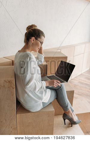 Beautiful Fashionable Businesswoman Working With Laptop While Sitting On Wooden Cubes