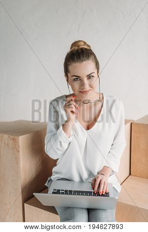 Beautiful Stylish Businesswoman In Eyeglasses Working With Laptop While Sitting On Wooden Cubes