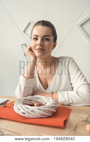 Smiling Beautiful Female Decorator With White Wreath At Workplace