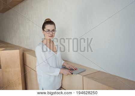 Beautiful Stylish Businesswoman Holding Laptop While Standing In Modern Office