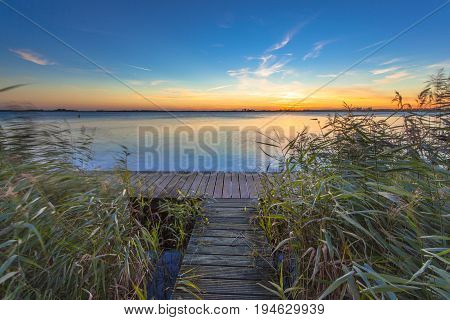 Long Exposure Image Of Sunset Over Boardwalk On The Shore Of A Lake