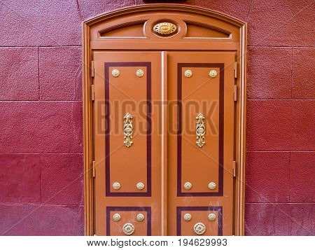 Part of building exterior shows brown door with golden door knob on red wall.