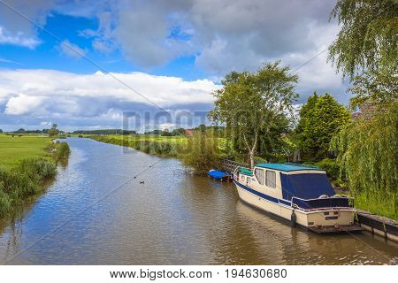 Yacht in straight canal of Friesland Netherlands