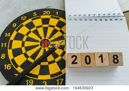 Year planning target or goals concept with wooden blocks number 2018 on note paper and dart board and pencil.