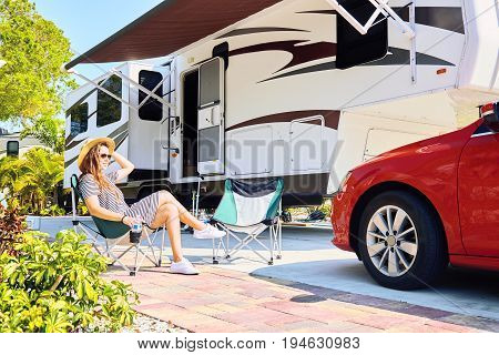 Young Woman Sits On Chair Near Camping Trailer And Car