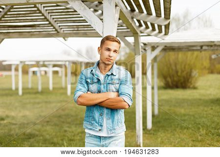 Handsome Young Man In A Jeans Jacket Near A Wooden Beach Canopy