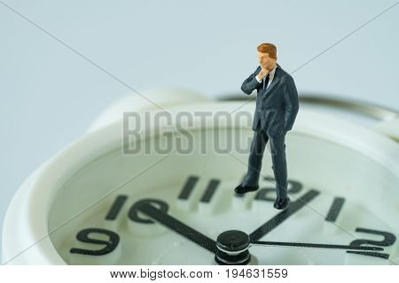 business or time countdown concept with miniature businessman thinking figure standing on white alarm clock.