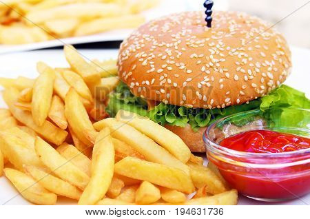 Burger with french fries and bowl of ketchup on white plate.