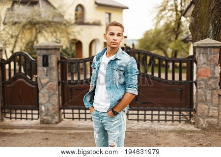 Handsome Young Man In A Stylish Vintage Denim Jacket And Ripped Jeans In The Courtyard Near The Fenc