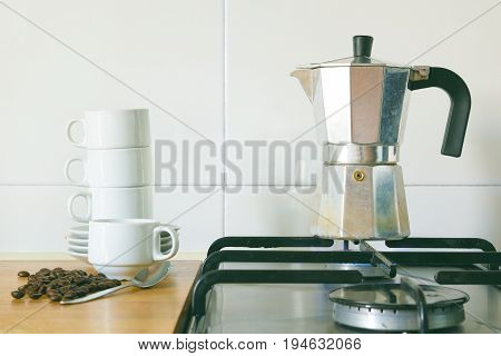 Preparing some coffee with a kettle on a burner of a rustic kitchen, next to a pile of cups and some grains. Empty copy space for Editor's text.