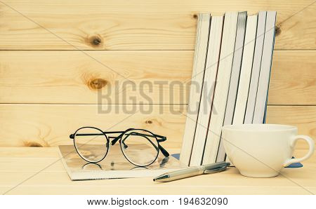 Books with glasses above. Book with glasses and coffee cup on table and wooden background concept for education.
