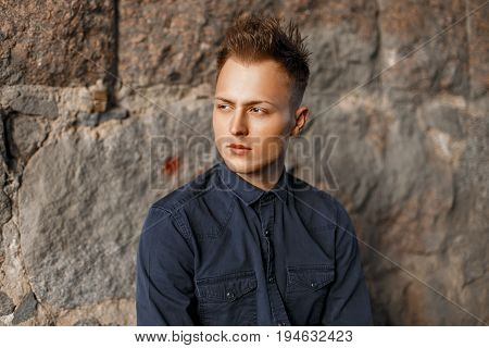 Handsome Young Man Looking Sideways Near A Stone Wall