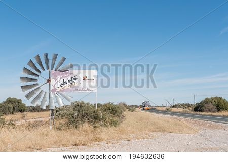 CAMPBELL SOUTH AFRICA - JUNE 11 2017: The wheel of a water-pumping windmill being used as part of a name board near Campbell a small village in the Northern Cape Province