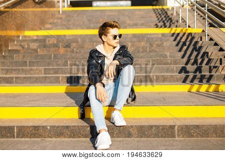Handsome Fashionable Young Man In A Black Leather Jacket And White Shoes Sitting On The Steps On A S