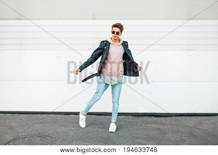 Handsome Young Fashionable Man With Sunglasses In A Black Leather Jacket, A Pink Sweatshirt, Blue Br