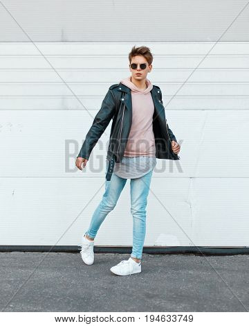 Young Guy In A Stylish Black Leather Jacket, A Pink Sweatshirt, Blue Gin And White Shoes In Motion