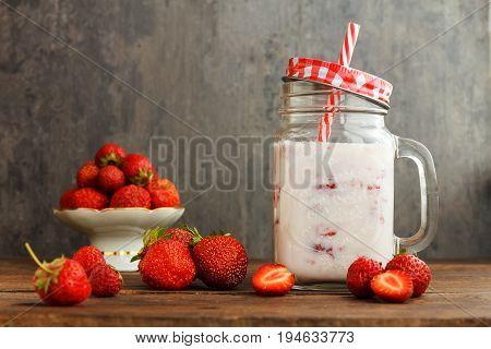 healthy strawberry smoothie or milkshake in jar on black rustic background, fresh food for breakfast and snack