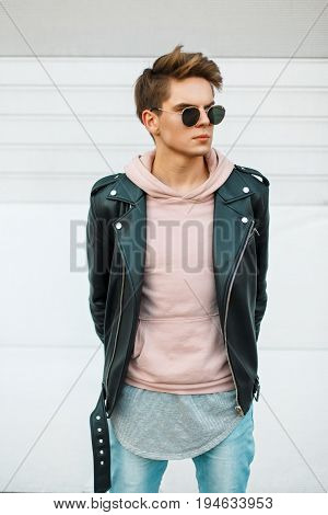 Handsome Young Fashionable Man With A Haircut In Sunglasses In A Leather Black Jacket And A Pink Swe
