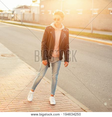 Fashionable Young Guy In Vintage Sunglasses In A Black Leather Jacket, Blue Jeans And White Sneakers