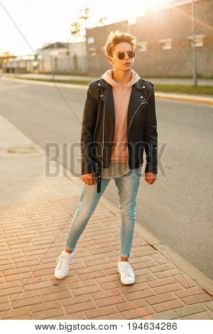 Handsome Young Guy With Sunglasses In A Leather Black Jacket And White Shoes At Sunset