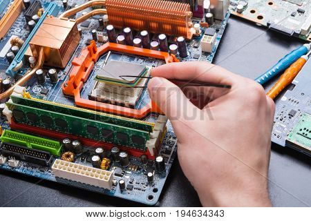 Computer processor chip disassembling in repair shop close up. Electronic service center, technology maintenance concept