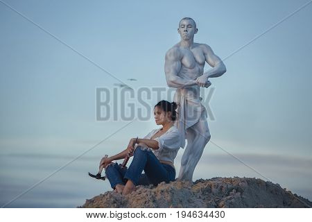 Woman has created a sculpture of a man and has a rest.