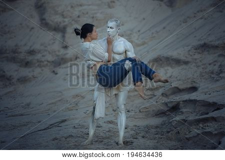 Sculpture of a man holds a woman in his arms they are in love.