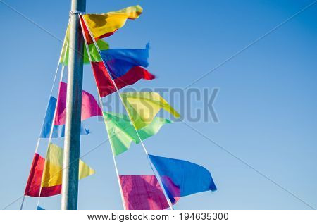 Dangling in the wind festive flags on the background of blue sky