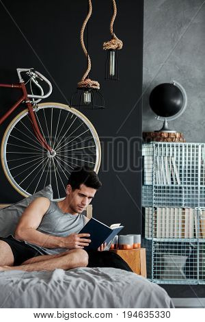 Handsome young man relaxing on a bed with book