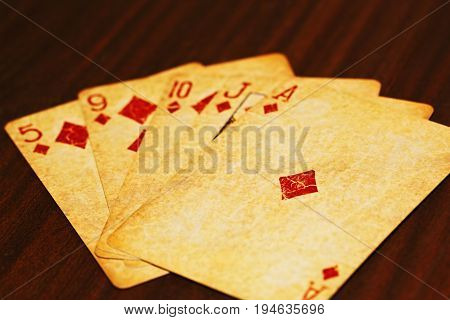 Five poker cards in a flush on the wooden table
