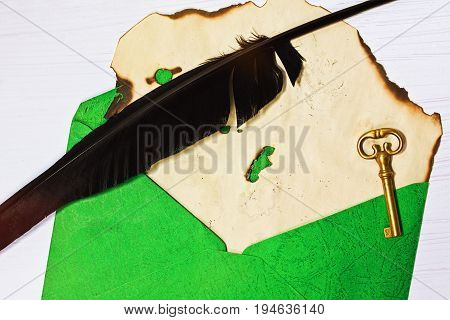Burnt piece of paper with quill and copper key in the envelope in horizontal top view