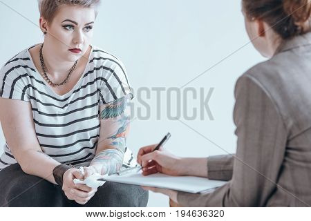Girl holding a tissue while listening to her counselor