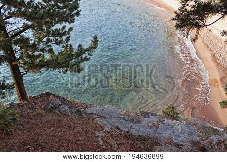 Top view of a small cove. Sheer cliffs turquoise sea