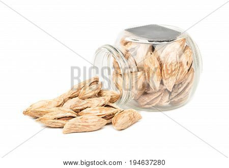 Scattered uzbek almonds from a jar isolated on white background