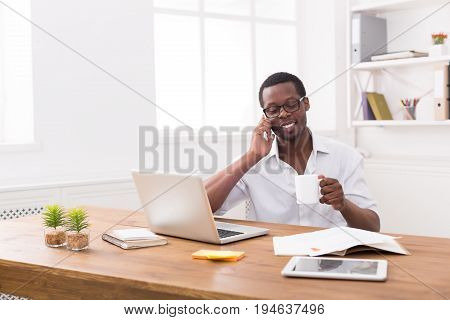 Mobile phone call. Young black businessman having a pleasant conversation while coffee break