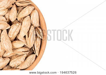 Part of a wooden bowl with uzbek almonds on white background, top view