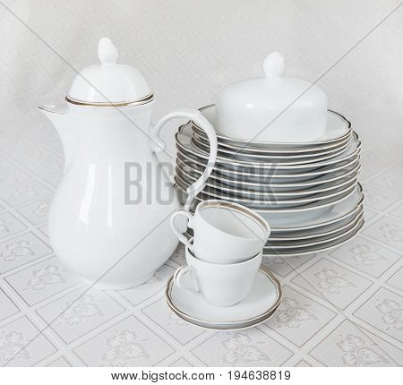 White crockery for tea: teapot cup serving plate and sugar bowl on a beautiful tablecloths