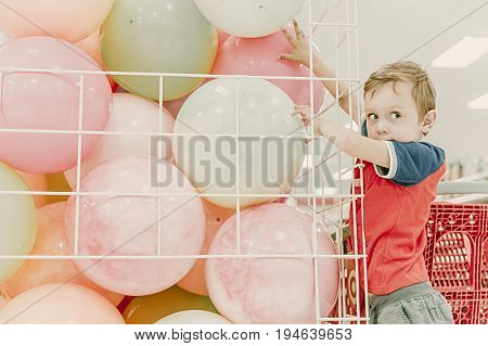 little boy trying to get the ball in the shop. young shopper in the store