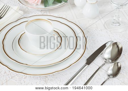 Beautifully decorated table with white plates crystal glasses linen napkin cutlery and rose flowers on luxurious tablecloths