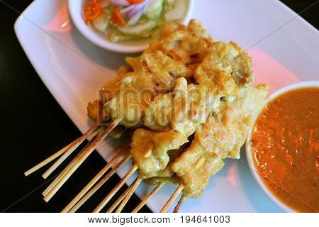 Tow view of Grilled Pork Satay with Spicy Peanut Sauce and Pickled Vegetable