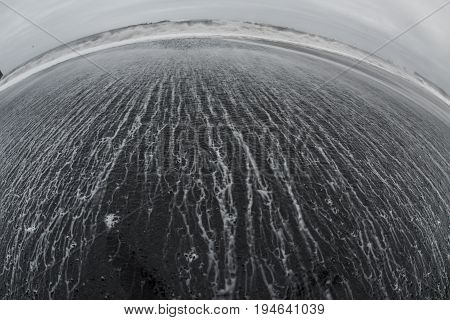 Volcanic rock on black sand beach at Vik in southern Iceland with waves sliding down the rocks