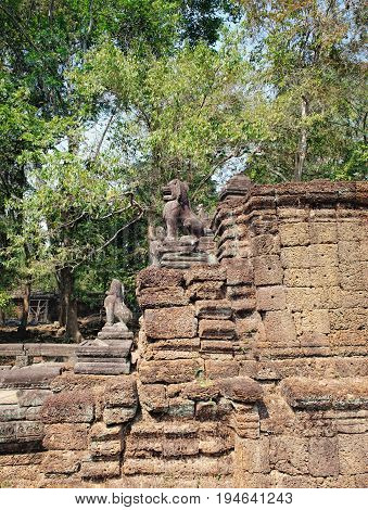 Lions in the foreground guarding Preah Khan Temple in Angkor Complex, Siem Reap, Cambodia. Ancient Khmer architecture and famous Cambodian landmark, World Heritage.