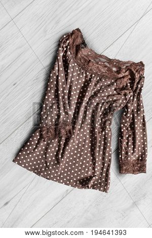 Brown silk polka dots blouse crumpled on white wooden background